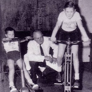 Cureton and 2 children on stationary bikes