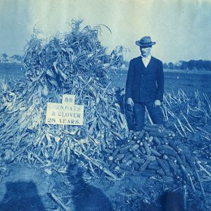 Hopkins standing next to a pile of corn husks